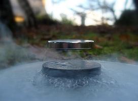 A magnet levitating above a disc of cuprate superconducting material - Lévitation d'un aimant placé au dessus d'une pastille de supraconducteur cuprate de type YBaCuO (Yttrium, Baryum, Cuivre, Oxygène) refroidie dans de l'azote liquide à -196°C.© CNRS Photothèque / Julien BOBROFF